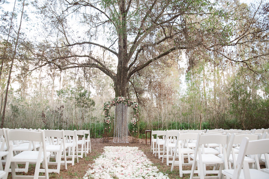 Rustic Outdoor Wedding Ceremony With Light Pink And White Fl Archway Under Tall Pines