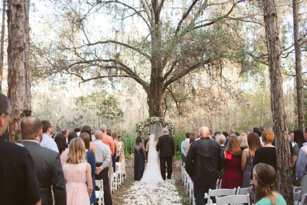 Rustic Outdoor Wedding Ceremony with Light Pink and White Floral Archway under Tall Pines with White Resin Folding Chairs and Rose Petal Aisle in Woods | Tampa Bay Wedding Florist Northside Florist