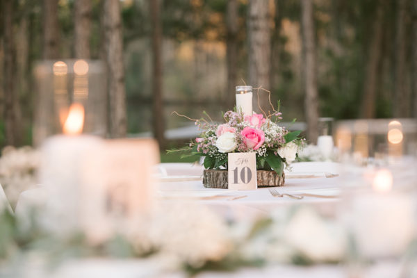 Outdoor Rustic Wedding Reception Centerpieces with Pink, Ivory and White Roses, Baby's Breath and Greenery on Wood Rounds with Light Pink Tablecloth | Tampa Bay Wedding Floral Designer Northside Florist
